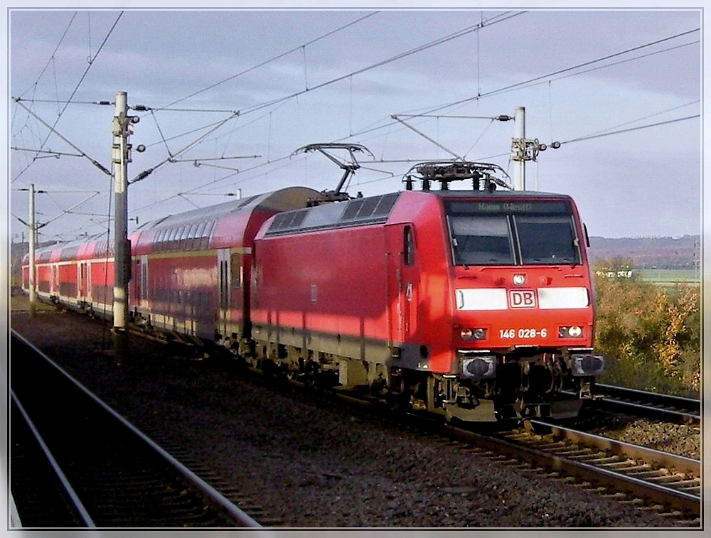 146 028-6 is running with bi-level cars through the station Köln-Weiden West on November 6th, 2007.