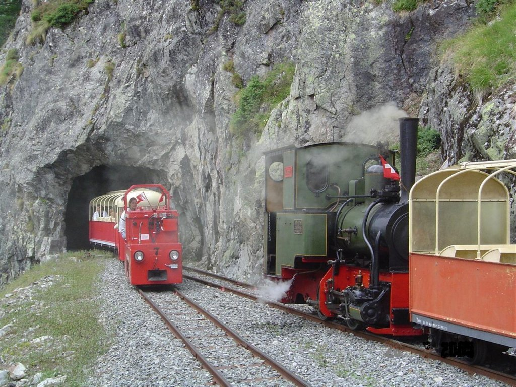 2 ft gauge steam engine  Liseli  (Jung No 1693, built 1911) in service on the high alpin panoramic railway of  Parc d'Attractions du Chatelard (VS)  in Switzerland. In the crossing station No 2. A electric regular train is comming from the station  Pied du Barrage , just leaving tunnel No 3 on its way to the station  Les Montuires . The steam train awaits the crossing. 26 July 2005