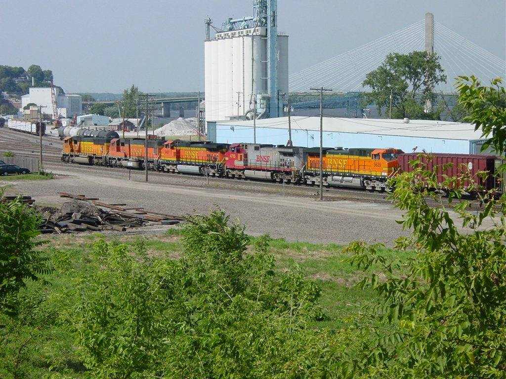 BNSF 8825, 8253, 5457, Santa Fe 4710 & BNSF 5635 pull their train into the Burlington, Iowa yard on 26 July 2003. The blue building is the former Rutherford Potato Co. now leased to a maintenance company. The grain elevator is part of the former ADM complex that exploded in the spring of 1985.