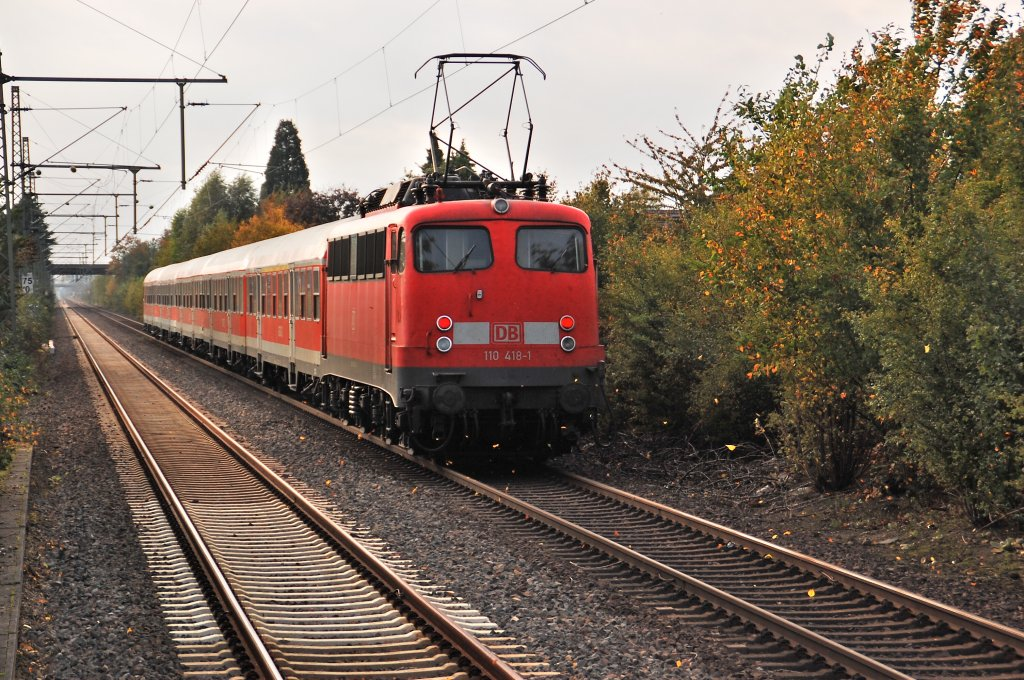 On that grey and rainy afternoon the class 11o 418-1 passes straight the station Büttgen/Germany by, with it's supporttrain at Line RE4 to Aachen. The main trains at the RE4 line build by 5 doubbledecker coaches and an class 111 or 112 locomotive. October 10th 2011