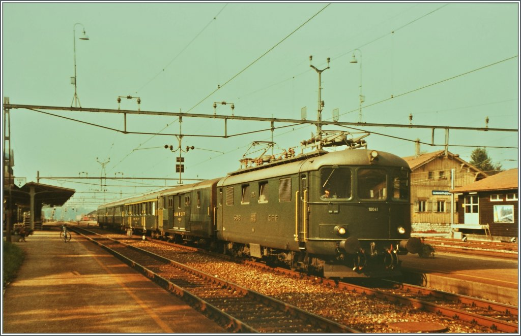Re 4/4 I 10041 with a fast train to Delemont by the stop in Grenchen Nord.