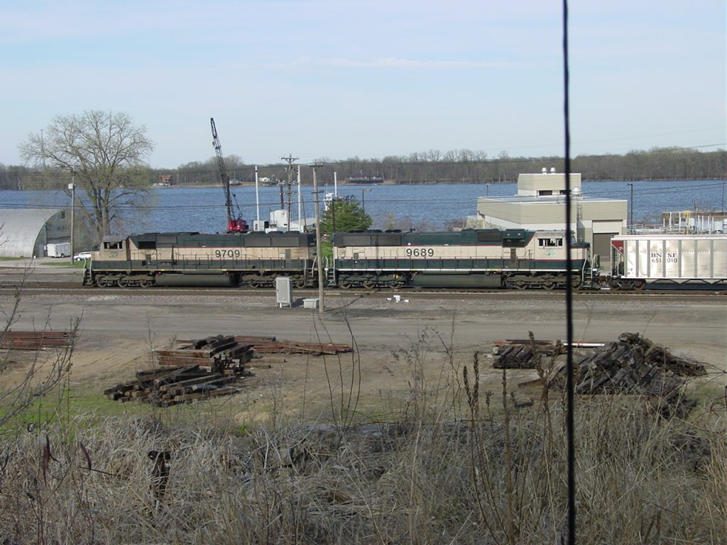SD70MAC Burlington Northern 9709 & 9689 roll through the Burlington, Iowa yard with 117 empty aluminum coal cars on 9 Apr 2005. Mississippi River in background.