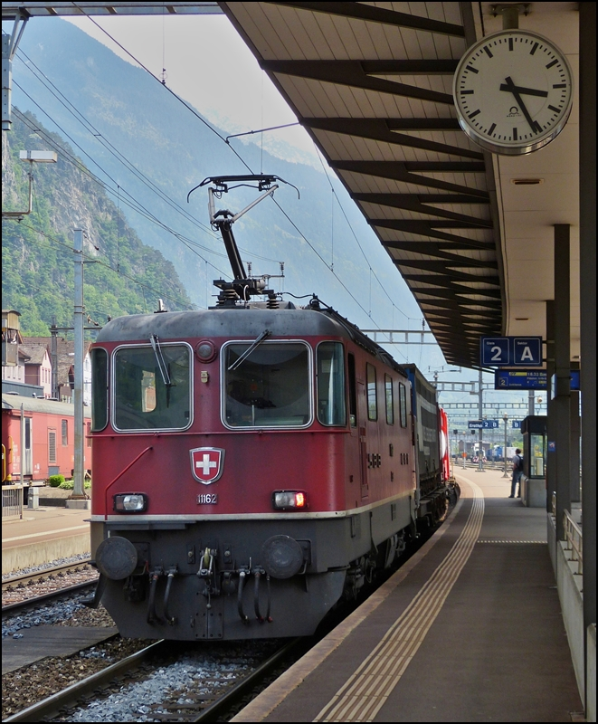 The Re 4/4 II 11162 is hauling a goods train through the station of Erstfeld on May 24th, 2012.