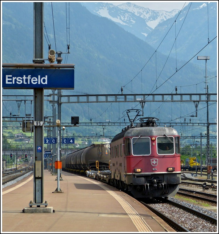 The Re 4/4 II 11634 is hauling a freight train through the station of Erstfeld on May 24th, 2012.