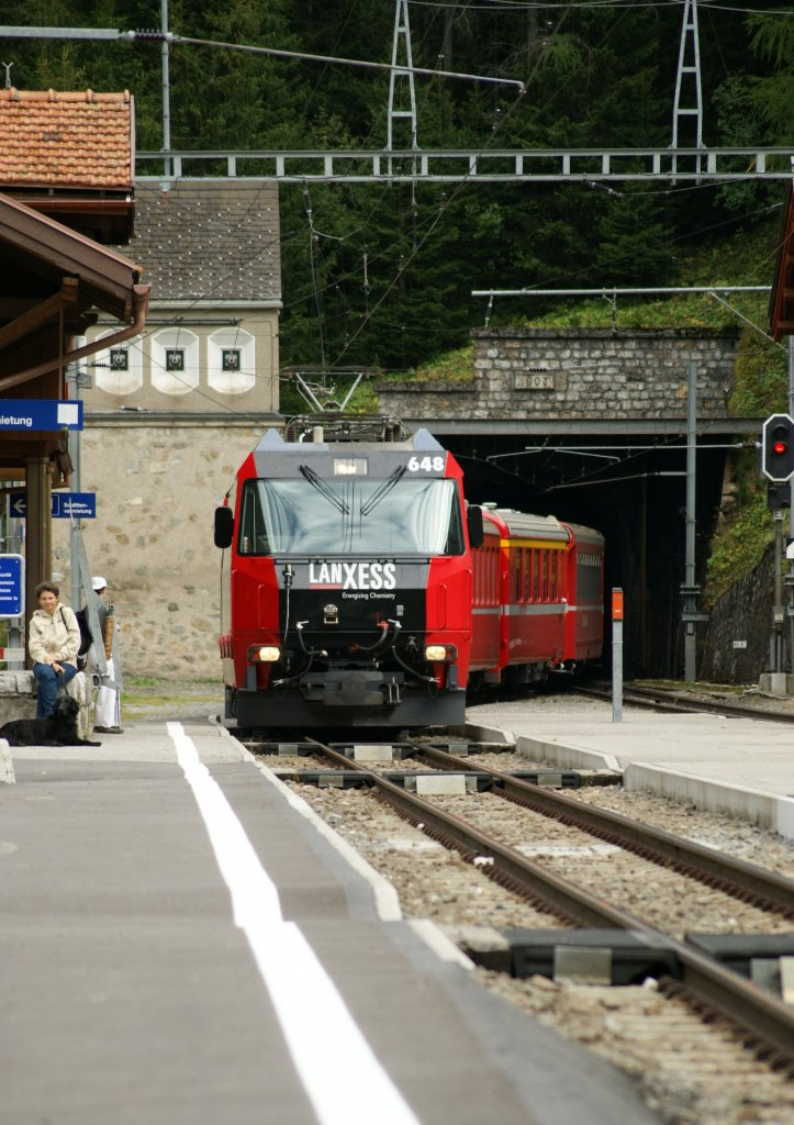 The RhB Ge 4/4 III 648 is coming out of the Albula Tunnel and arriving with his RE to Chur in Preda.
