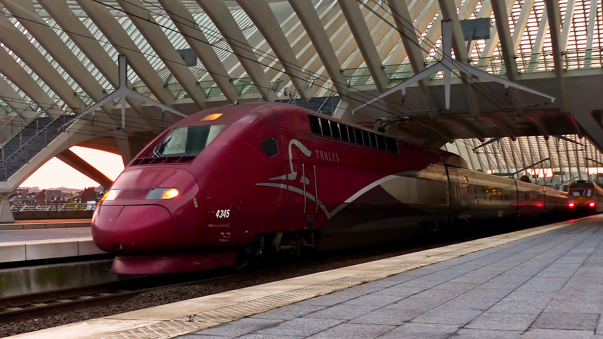 . The PBKA Thalys 4345 is leaving the station Liège Guillemins while the sun is rising on October 18th, 2014.