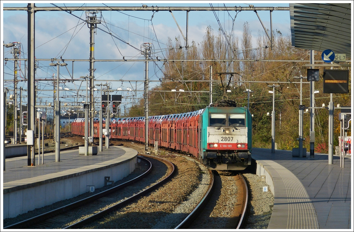 . The TRAXX HLE 2807 is hauling a freight train through the station of Brugge on November 23rd, 2013.
