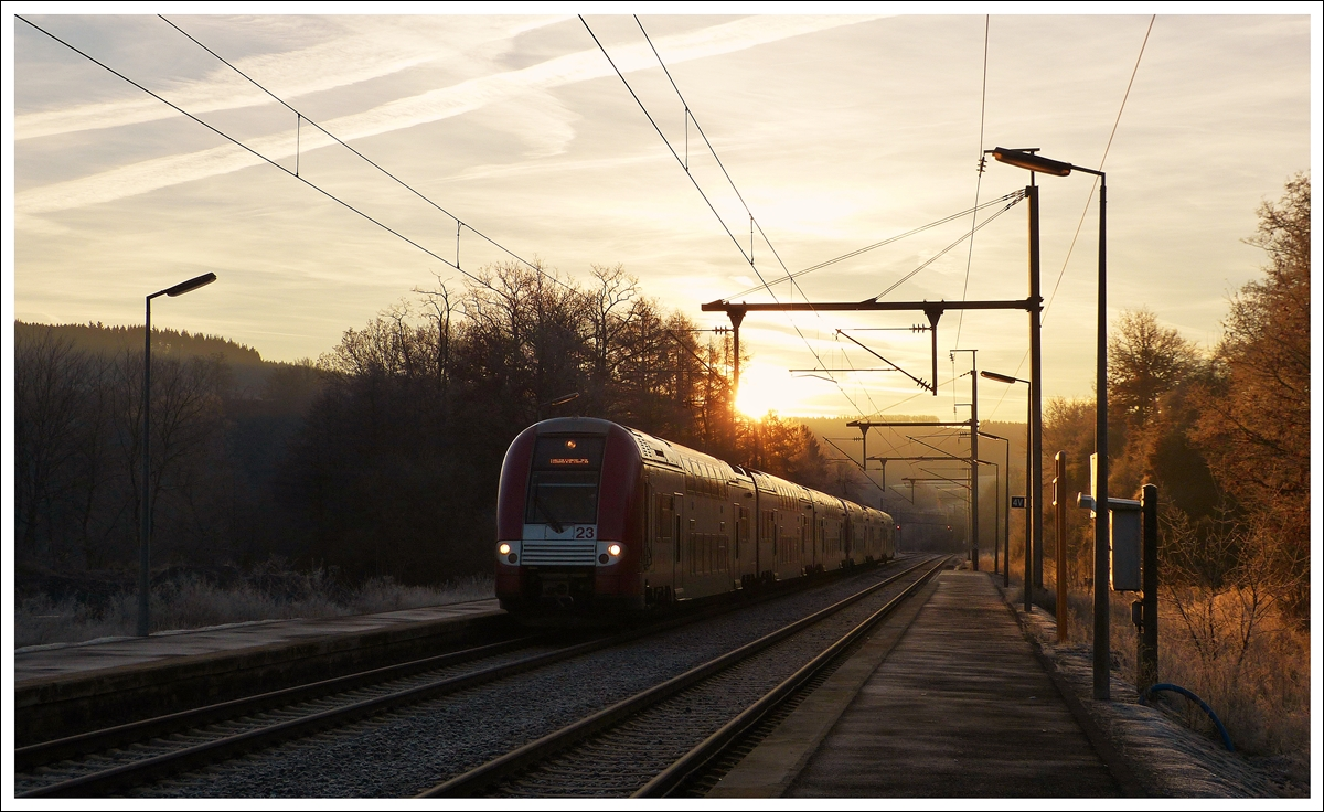 . While the sun is rising on the cold December 16th, 2013 morning, the IR 3708 Luxembourg City - Troisvierges is entering into the station of Wilwerwiltz.