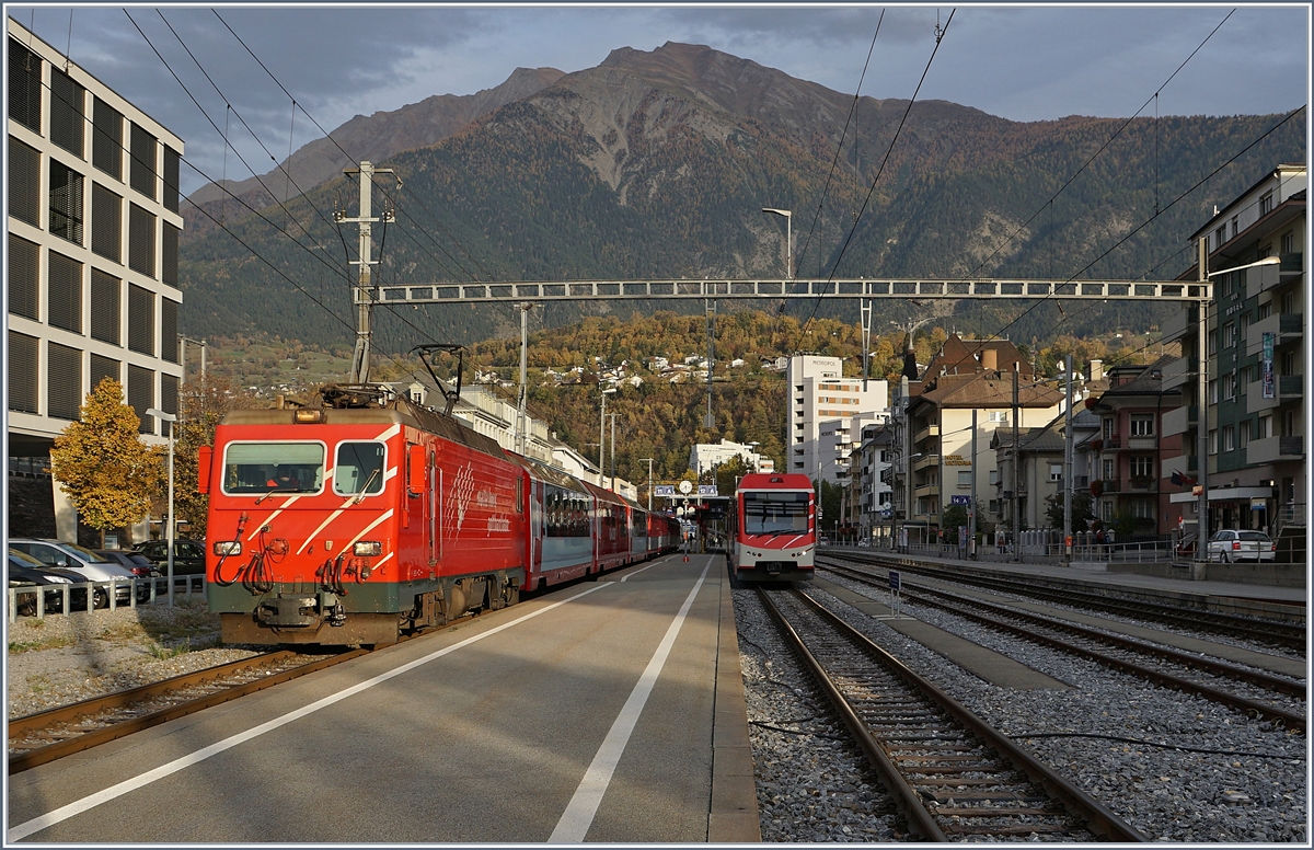 A MGB HGe 4/4 II with an local train to Visp by his stop in Brig. This train service has on this day two Glaicer-Express wagons for a Group.