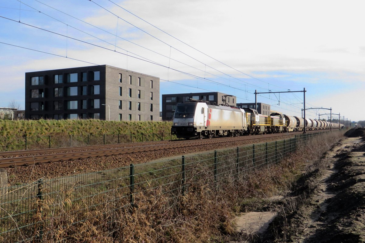 Akiem 186 387 and two SNCB Class 77 haul a diverted dolime train through Tilburg-Reesghof on 21 February 2021.