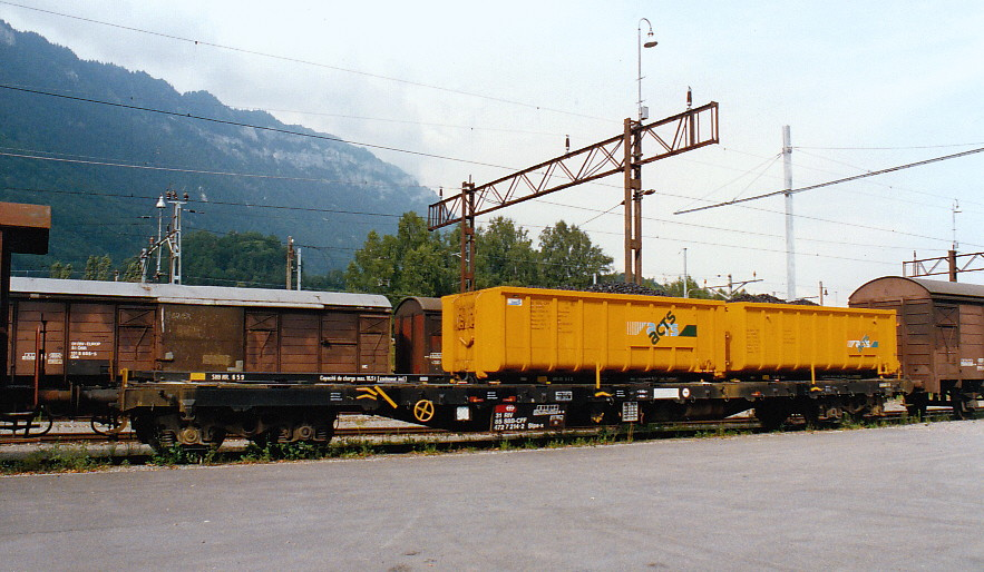 SBB-CFF Flat Wagon Slps-x used for hauling Roll-off Containers (ACTS Containers), near station Interlaken-Ost (CH), August 1993