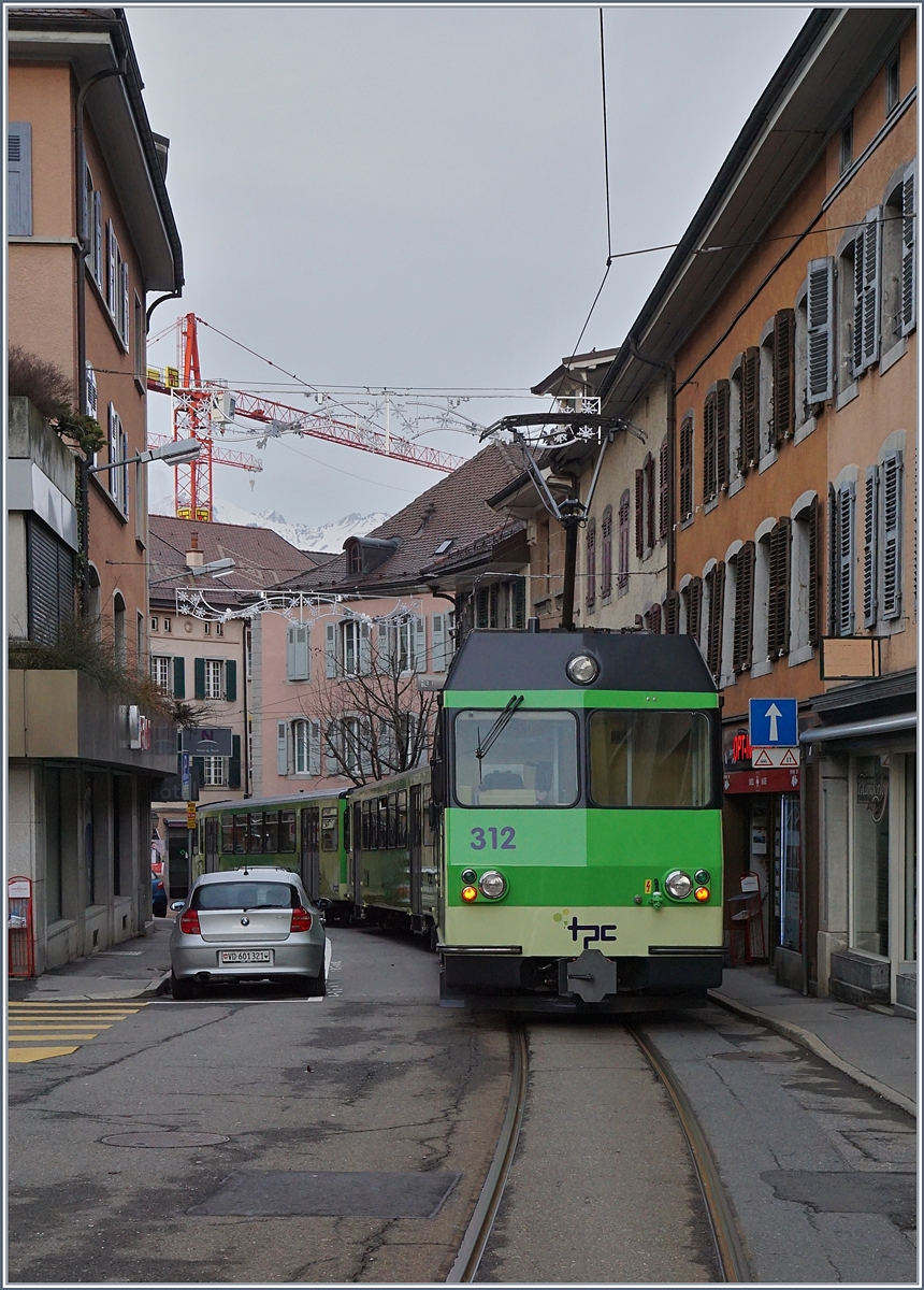 The A-L BDeh 4/4 412 with his train to the Aigle Station in the streets of Aigle.