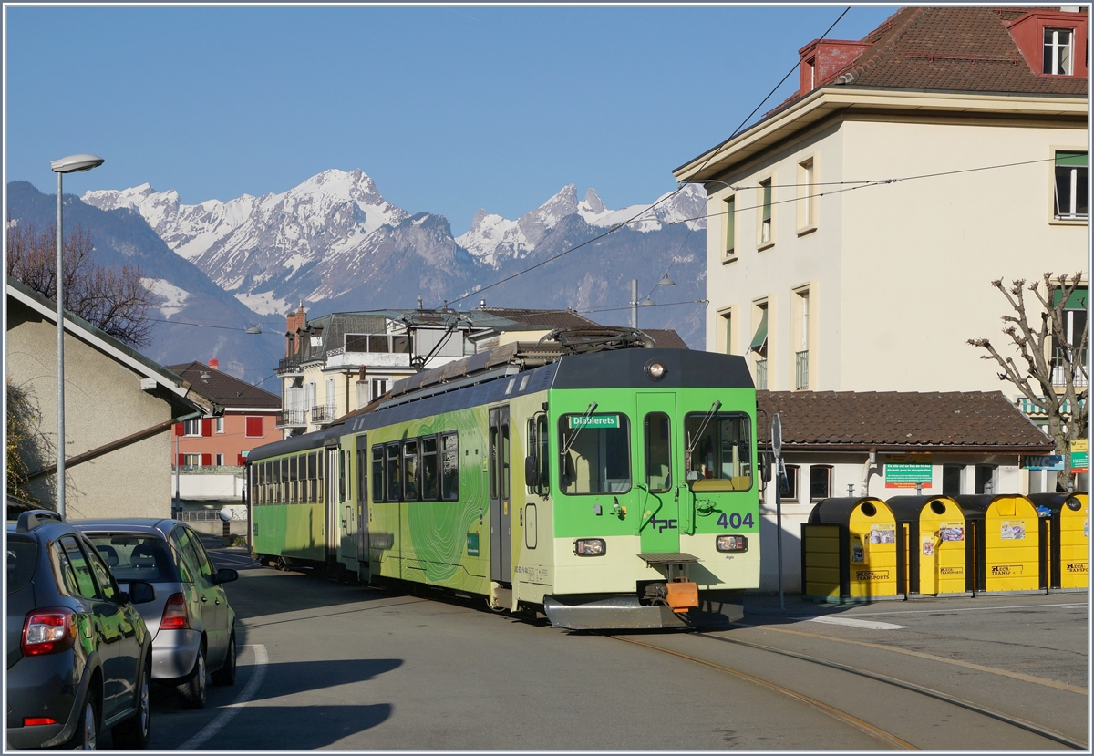 The ASD BDe 4/4 404 wiht his Bt by a stop at Aigle Place du Marché ASD.
