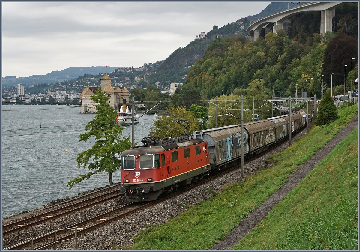 The SBB Re 420 278-4 with a Cargo Train near Villeneuve, in the background the Castle of Chillon.