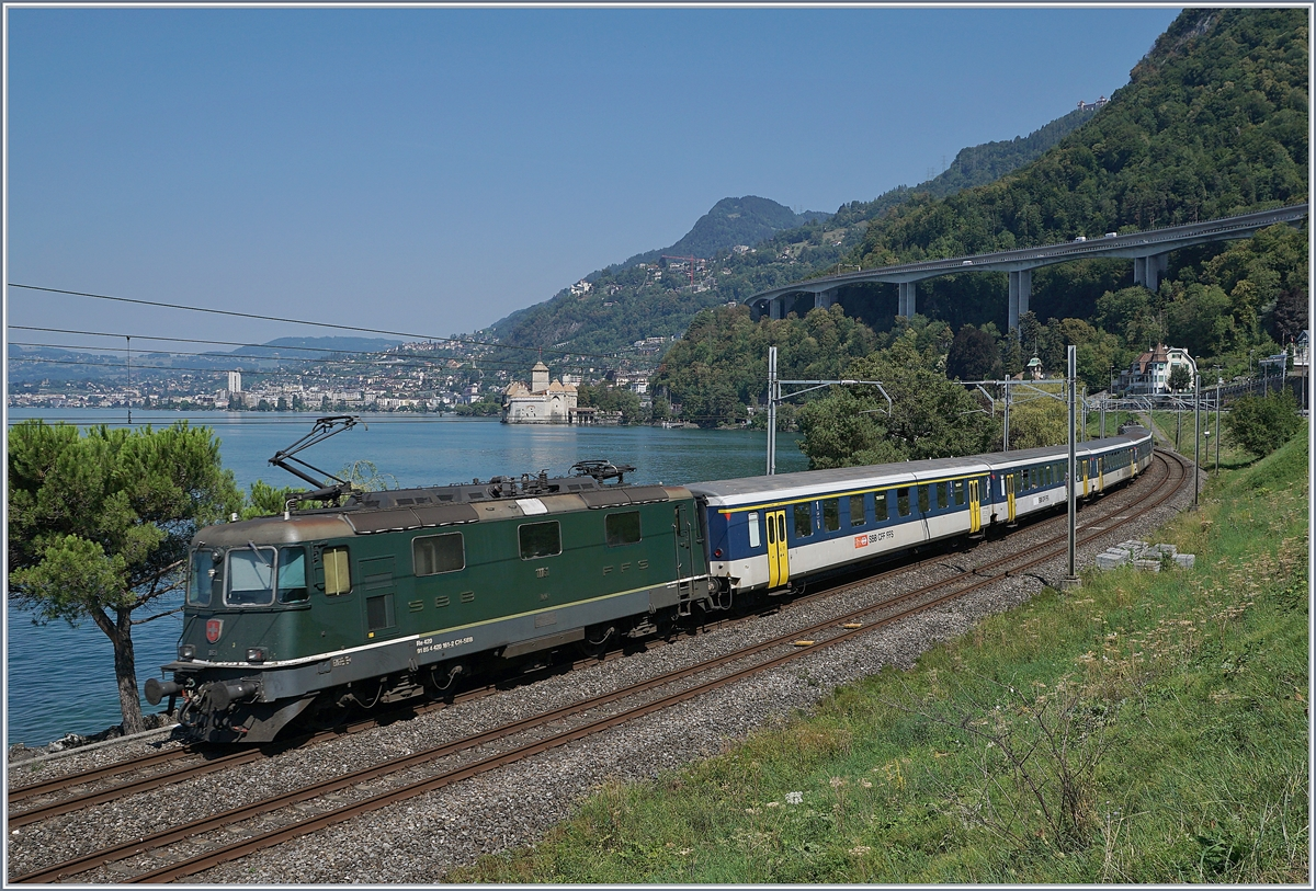 The SBB Re4/4 II 11161 with a Dispozug by the Castle of Chillon.