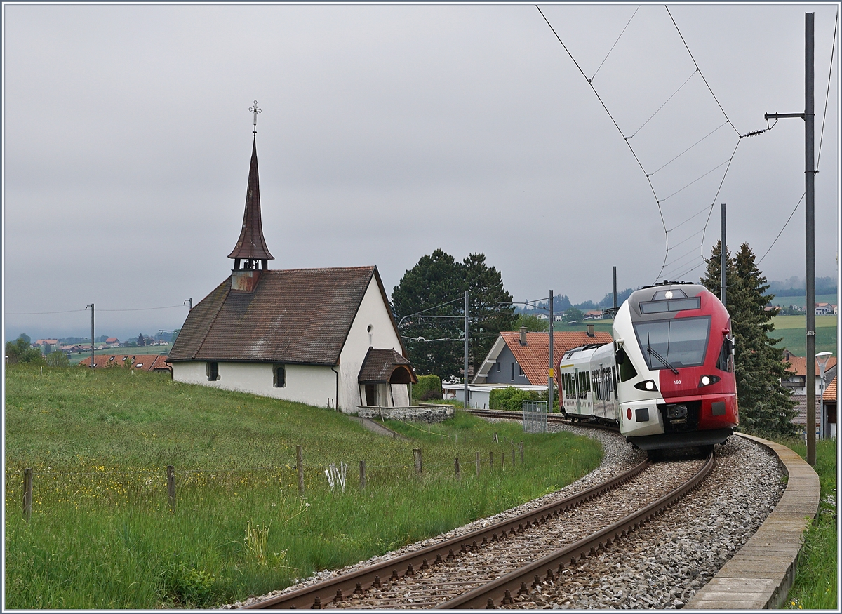 The TPF Flirt RABe 527 193 on the way to Fribourg by Vaulruz. 