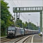 MRCE 185 565-9 is hauling the NIAG 216 111-5 and goods wagons through the station of Remagen on July 28th, 2012.