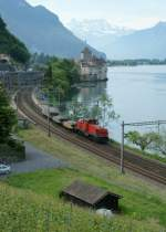 An Am 841 with a short Cargo train by the castle of Chillon.