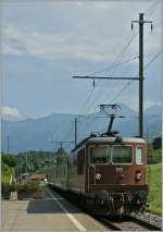 BLS Re 4/4 195 with a local train to Interlaken is leaving Faulensee.