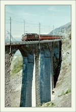A analog picture with a BLS Re 4/4 and his EC  Monteverdi  to Venezia on the Luogelkinn Bridge by Hotenn (BlS South Ramp).