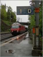 It's raining by the arriving on the SBB Re 460 015-1 with his IR in Vevey on the platform 1.