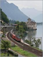 The SBB Re 620 017-4 with the Novelis Cargo train by the Castle of Chillon.