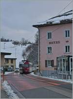 The TPF local train with the Be 4/4 121, B 207, B209 and ABt 221 on the way to Bulle in the streets of Montbovon.